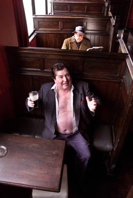Photograph of Oliver Moore as Brendan Behan (front) with Ken McElroy as Patrick Kavanagh (behind), taken in a bar